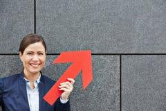 Geschäftsfrau, die roten Pfeil hochhält Lizenzfreies Stockfoto