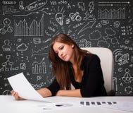 Geschäftsfrau, die am Schreibtisch mit Geschäftsentwurf und -ikonen sitzt Stockfoto