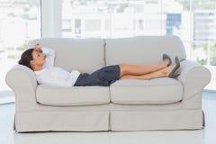 Geschäftsfrau, die sich auf der Couch hinlegt Stockfoto