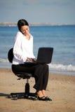 Geschäftsfrau, die am Strand arbeitet Lizenzfreie Stockbilder
