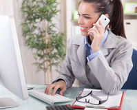 Geschäftsfrau, die am Telefon im Büro spricht und an Baut. arbeitet Stockfotografie