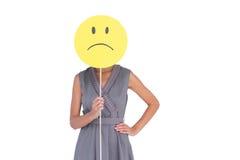 Geschäftsfrau, die trauriges smileygesicht hält Stockbilder