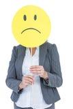 Geschäftsfrau, die trauriges smileygesicht hält Stockfotografie