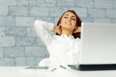 Geschäftsfrau, die vor ihrem Arbeitsplatz ausdehnt Stockbilder