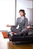 Geschäftsfrau, die Yoga in einem modernen Büro tut Stockbild