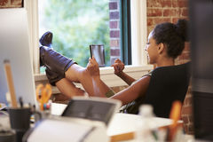Geschäftsfrau With Digital Tablet, das im modernen Büro sich entspannt Lizenzfreie Stockfotografie