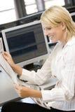 Geschäftsfrau-Lesezeitung am Arbeits-Schreibtisch Stockfotos