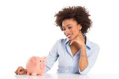 Geschäftsfrau, die Piggybank betrachtet Stockbild