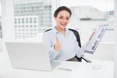 Geschäftsfrau mit Diagrammen und Laptop, die Daumen oben im Büro gestikulieren Lizenzfreies Stockbild