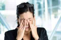 Geschäftsfrau mit müden Augen und Druck Stockfotos