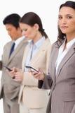 Geschäftsfrau mit Mobiltelefon nahe bei Kollegen Lizenzfreies Stockbild
