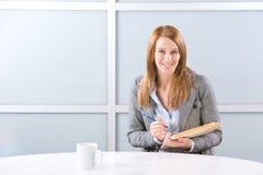 Geschäftsfrau-Schreibensanmerkungen am Schreibtisch Stockfotografie