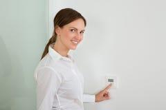Geschäftsfrau Setting The Temperature auf Digital-Thermostat Stockfoto