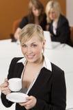 Geschäftsfrau-trinkender Kaffee in einem besetzten Büro Stockbilder