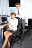 Geschäftsfrau und ihr Kollege, die im Büro arbeiten Stockbilder