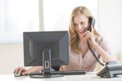 Geschäftsfrau Using Computer While, das am Überlandleitungs-Telefon sich unterhält Stockfoto