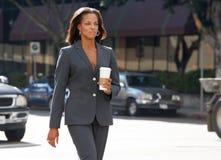 Geschäftsfrau Walking Along Street, das Mitnehmerkaffee hält Stockfotografie