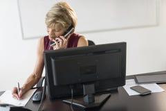 Geschäftsfrau Writing On Document bei der Anwendung des Überlandleitungs-Telefons Stockbilder