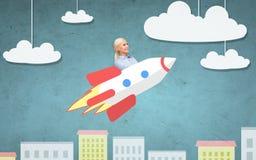 Geschäftsfraufliegen auf Rakete über Karikaturstadt Stockfotos