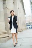 Geschäftsfraugespräch zum Handy und Gehen an der Straße Lizenzfreie Stockfotografie