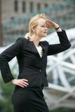 Geschäftsfraugruß mit der Hand zum Kopf, der in der Stadt schaut Lizenzfreies Stockfoto