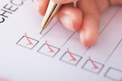Geschäftsfrauschreiben auf Checkliste Stockfotografie