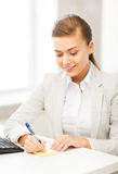 Geschäftsfrauschreiben auf klebriger Anmerkung Stockfotografie