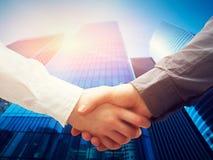 Geschäftshändedruck, Wolkenkratzerhintergrund. Abkommen, Erfolg, Zusammenarbeit Stockfotografie