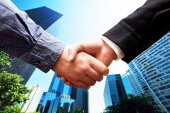 Geschäftshändedruck, Wolkenkratzerhintergrund. Abkommen, Erfolg, Zusammenarbeit Stockbild