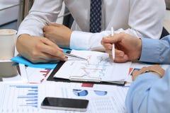 Geschäftskollegen, die zusammenarbeiten und Finanzfeige analysieren Lizenzfreie Stockbilder