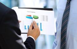 Geschäftskollegen, die zusammenarbeiten und Finanzfeige analysieren Lizenzfreies Stockbild