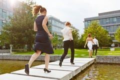 Geschäftsleute, die über eine Brücke laufen Stockbild