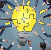 Geschäftsleute, die ein Glühlampe-Puzzlespiel bilden Stockfotos