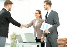 Geschäftsleute, die Hände in einem Büro rütteln Stockfotos
