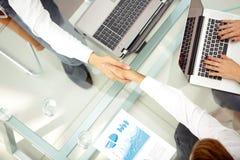 Geschäftsleute, die Hände während einer Sitzung rütteln Stockfotografie