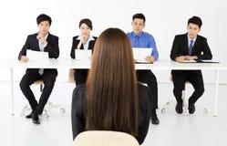 Geschäftsleute, die junge Geschäftsfrau im Büro interviewen Lizenzfreie Stockfotografie