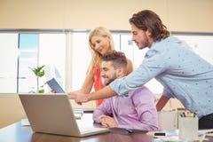 Geschäftsleute, die mithilfe des Laptops und der digitalen Tablette arbeiten Stockbild