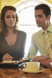 Geschäftsleute, die Zeitplan am Café vorbereiten Stockfoto