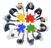 Geschäftsleute mit Puzzlen und Teamwork-Konzept Lizenzfreies Stockbild