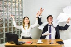 Geschäftsleute regten glückliches Lächeln, Wurfspapiere, Dokumente fliegen in einer Luft, die Wirtschaftler auf, die am Schreibti Stockbild