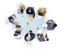 Geschäftsleute um den Konferenztisch Stockbilder
