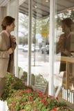 Geschäftsmann Adjusting Tie While, das Glaswand betrachtet Lizenzfreie Stockfotografie