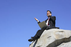 Geschäftsmann auf einem Felsen Stockfotografie