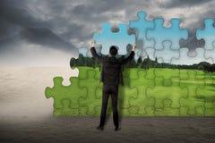 Geschäftsmann bauen Puzzlespiel zusammen, um von Wüste zu ändern zu Landschaft Stockfotografie