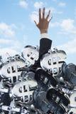 Geschäftsmann begraben unter einer großen Gruppe Dollarzeichen, versuchend hinauszugehen Stockfotografie