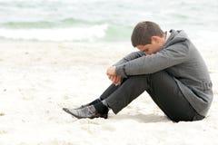 Geschäftsmann, der auf dem Strand alleine sitzt Stockfoto