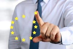 Geschäftsmann, der auf ein Zeichen der Europäischen Gemeinschaft drückt Lassen Sie den Euro Stockfotos