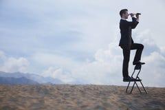 Geschäftsmann, der auf einem Stuhl steht und durch ein Teleskop mitten in der Wüste schaut Stockbilder