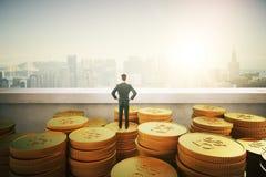 Geschäftsmann, der auf Goldmünzen steht Stockfotografie