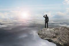 Geschäftsmann, der auf Klippe mit natürlichem Himmeltageslicht cloudscap schaut Lizenzfreie Stockfotos